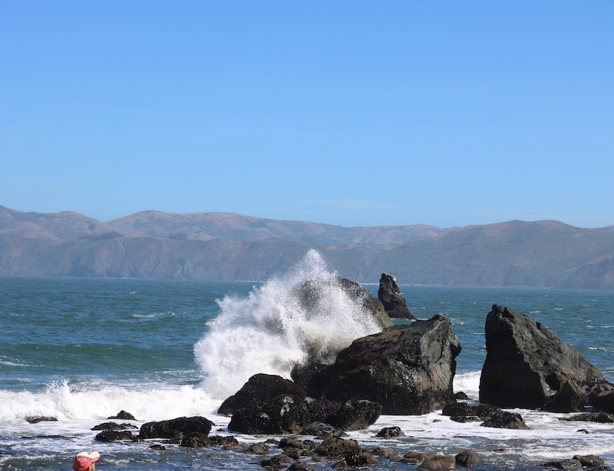 a wave in the Pacific Ocean at Lands End crashing into a rock at Mile Rock Beach in San Francisco, California
