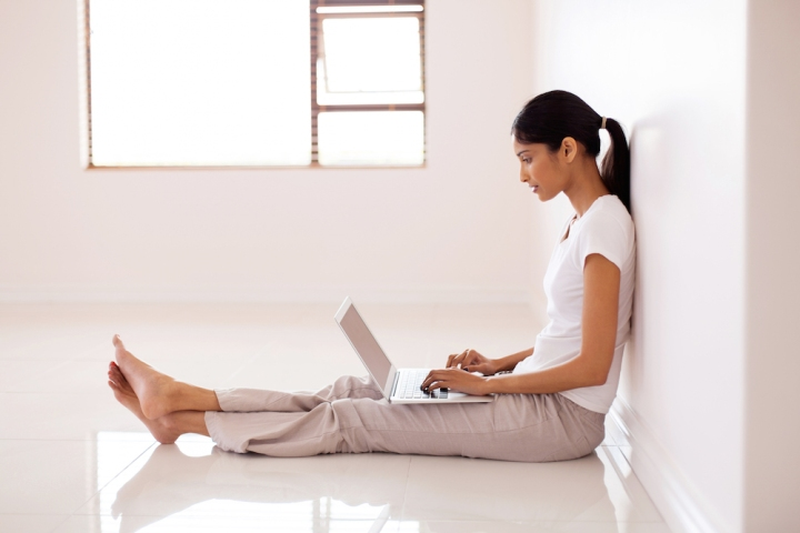 woman wearing white blouse and pants on computer