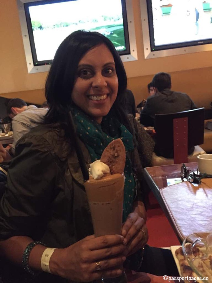 Girl smiling, holding a big chocolate milkshake