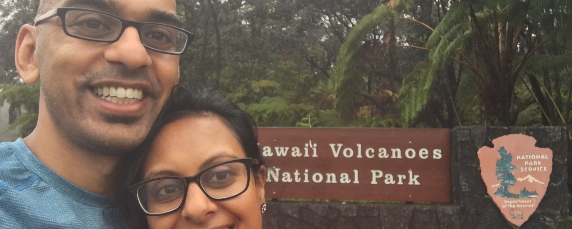 husband and wife standing in front of entrance to Hawaii Volcano National Park